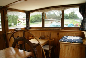 Wheelhouse looking aft. To right, hatch to rear cabin. Oak table folds up to seat four