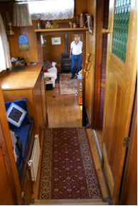 Looking forward from wheelhouse Head is to starboard, to port is window seat with storage below, washing machine & fridge (in wood cabinet)